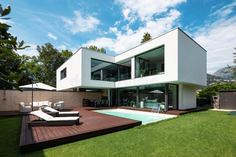 Buiten moderne witte villa met pool en tuin stock foto's