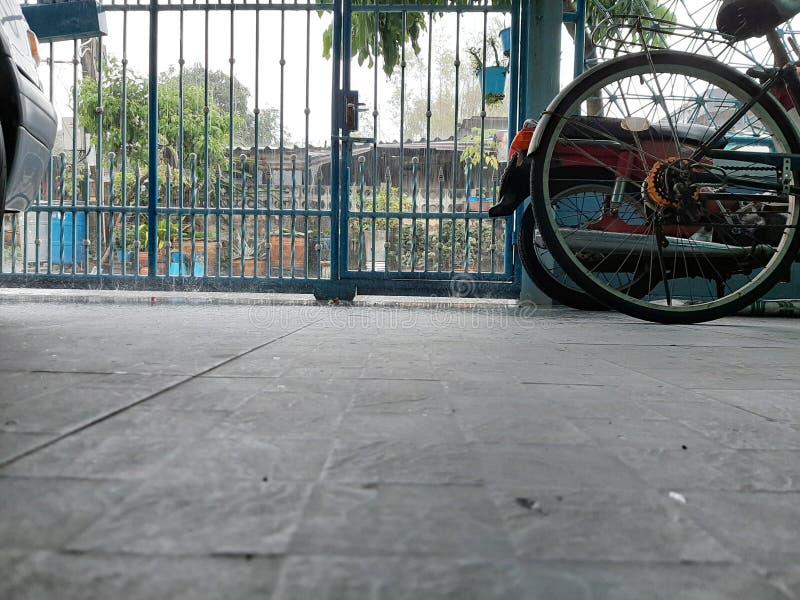 Buiten zicht door poort, druppel de regendruppels op arme bewoners en boompotten dichtbij de cementomheining royalty-vrije stock foto