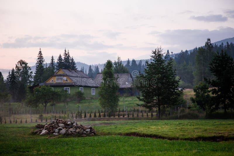 Buitenhuis in bergen Mist en bos rond royalty-vrije stock afbeelding