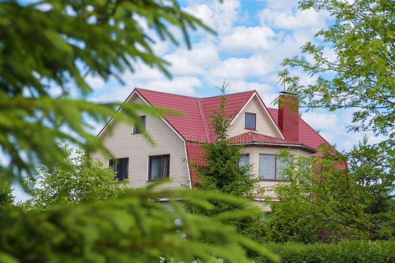 Buitenhuis dat door groene bomen op een de zomerdag wordt omringd royalty-vrije stock foto