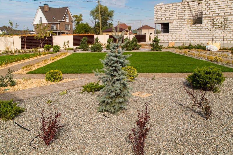 Buitenhuis en groen gazon Het ontwerp van het landschap stock afbeelding
