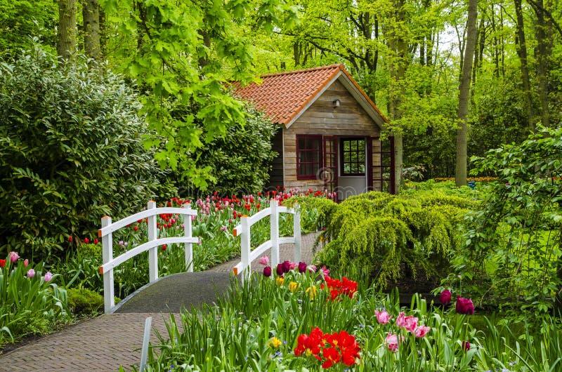 Buitenhuis en witte brug in Keukenhof-tuinen royalty-vrije stock foto