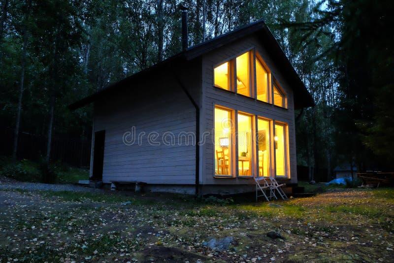 Buitenhuis in nachtbos stock fotografie