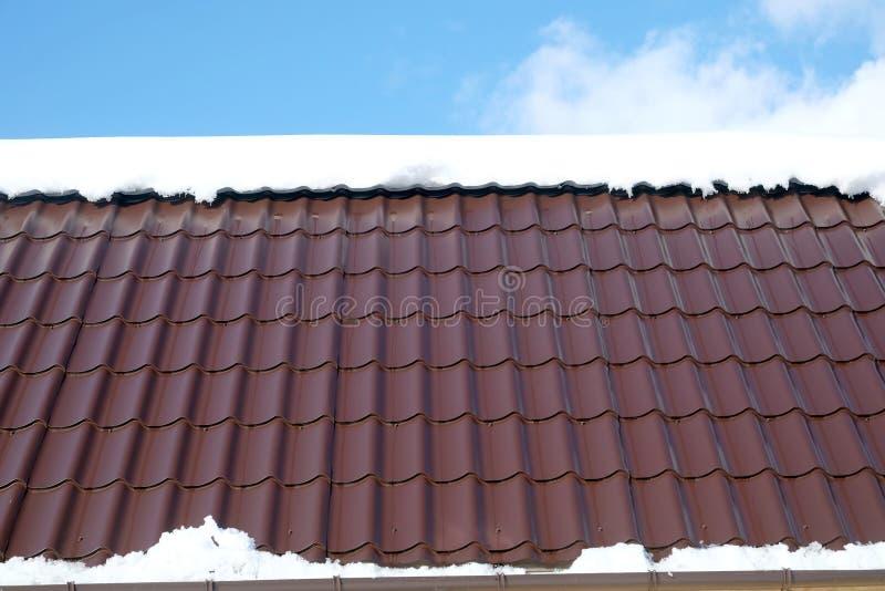 Buitenhuisdak van bruine metaaltegel met sneeuw in zonnige de lentedag onder blauwe hemel met witte wolken royalty-vrije stock fotografie