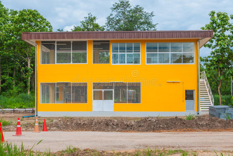 Buitenkant van de Lege Concrete Gele Bouw van het Fabriekspakhuis stock fotografie