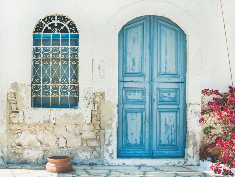 Buitenkant van Griekse eiland traditionele straat met blauwe deur, Kast stock afbeelding