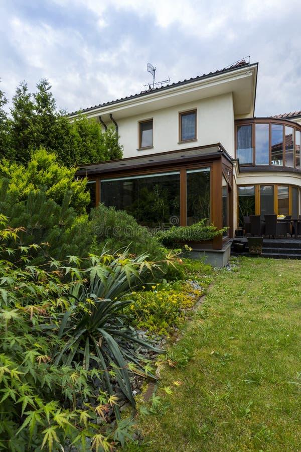 Buitenkant van huis door weelderig groen wordt omringd dat stock afbeelding