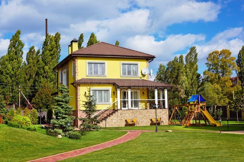 Buitenkant van mooi huis met groene werf en kinderenplaygro royalty-vrije stock foto's