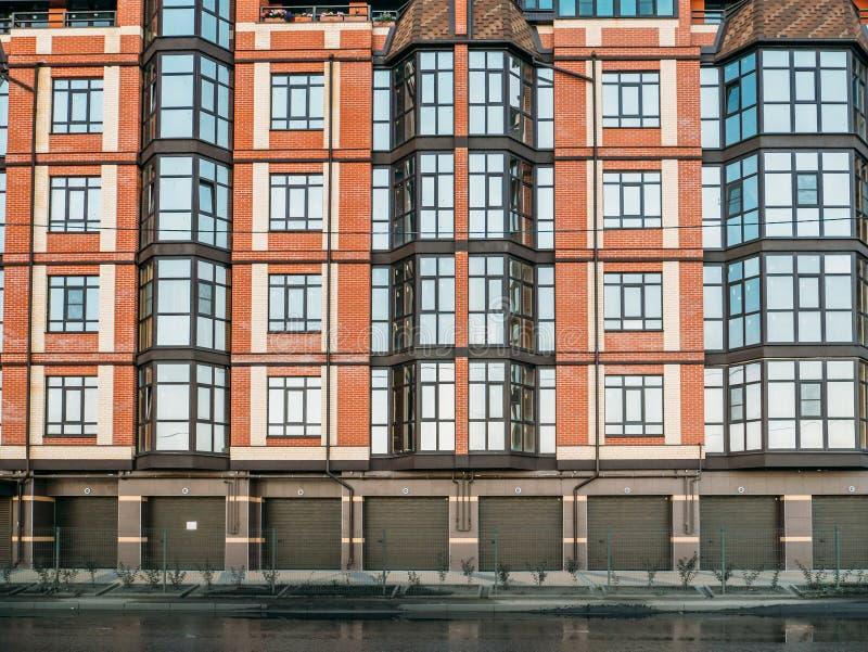 Buitenkant van nieuwe rode baksteen woonwoningbouw wordt geschoten met de poorten die van de parkerengarage stock afbeeldingen