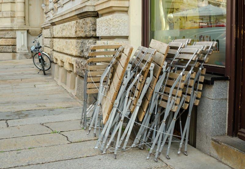 Buitenkoffie gestapelde stoelen voor nacht in Leipzig, Duitsland stock afbeeldingen