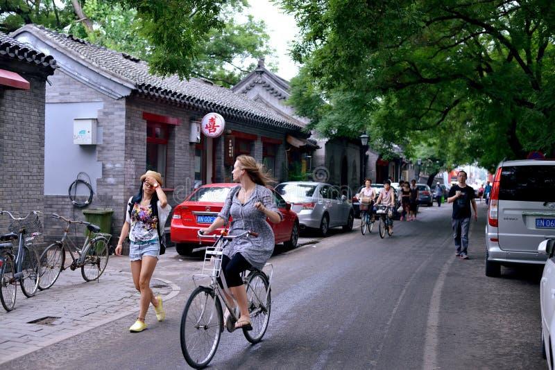 Buitenlands meisje die een fiets in Peking berijden hutongs royalty-vrije stock foto's