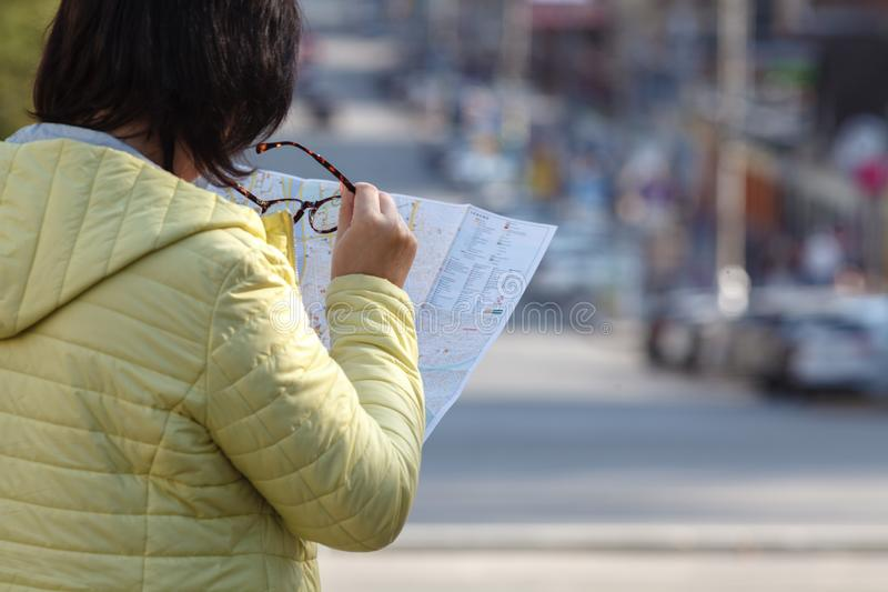 Buitenlands vrouwelijk model die op gedrukte document kaart op zoek naar F kijken royalty-vrije stock afbeeldingen