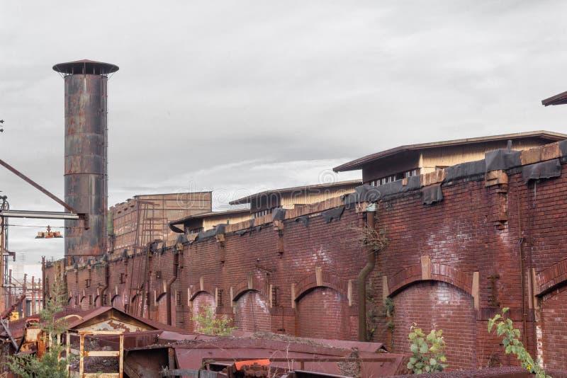 Buitenmening van een pakhuisdistrict, oude baksteenarchitectuur, schoorsteen, roestende metaalstructuren stock fotografie