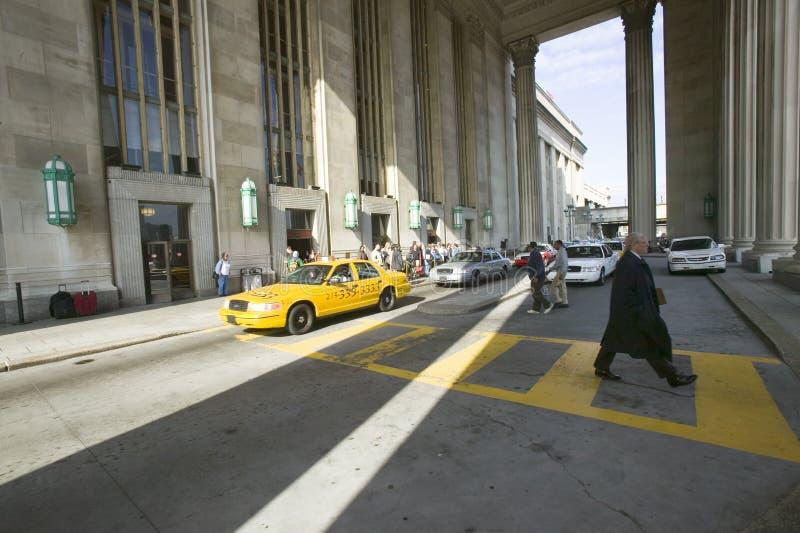 Buitenmening van gele taxicabine en de lopende bedrijfsmens voor de 30ste Straatpost, een nationaal Register van Historische Pl stock fotografie