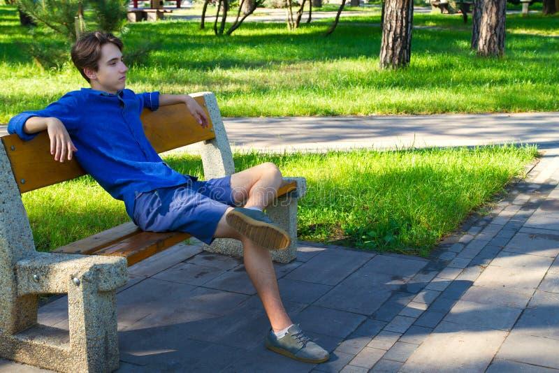 Buitenportret van de jonge mens in park Tiener die rust in park op de bank hebben stock foto