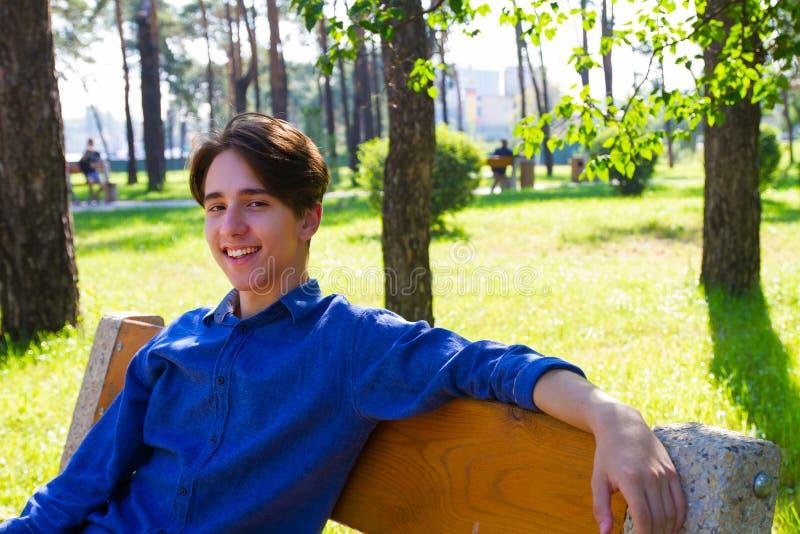 Buitenportret van de jonge mens in park Tiener die rust in park op de bank hebben stock fotografie