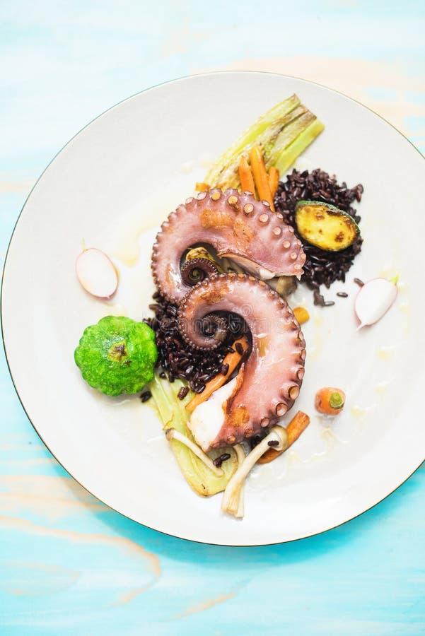 Buitensporig diner met octopus, groenten en zwarte rijst stock foto's