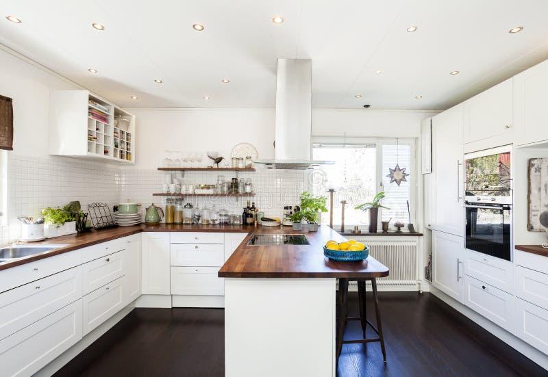 Buitensporig keukenbinnenland met houten tegenbovenkant en dar houten vloer witte kasten stock fotografie