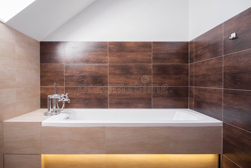 Buitensporige badkuip in toilet stock afbeeldingen