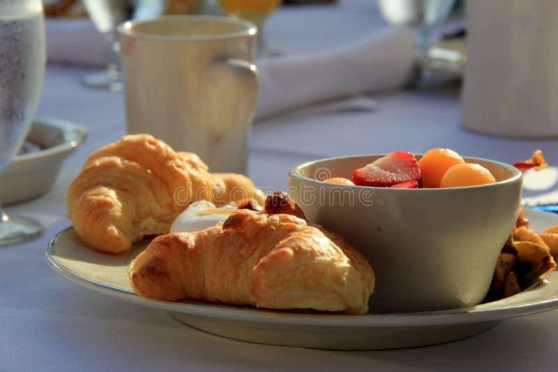 Buitensporige croissants en seizoengebonden fruit op plaat in het openlucht plaatsen stock foto's