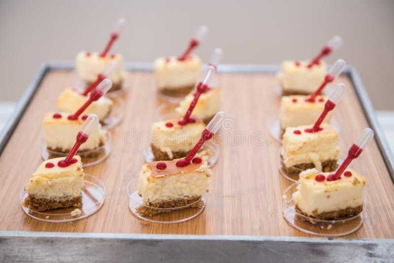 Buitensporige mooie minicakes op houten plaat op zelfs snacklijst stock foto's