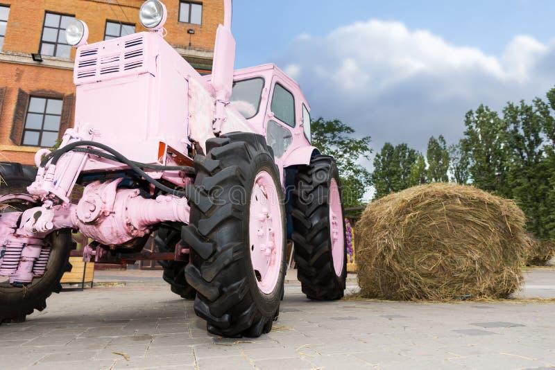Buitensporige roze tractor naast een hooiberg stock foto's