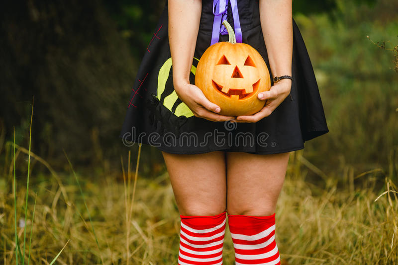 Buitensporige vrouw op Halloween in het bos, die in handenpompoen houden met gesneden gezicht stock fotografie
