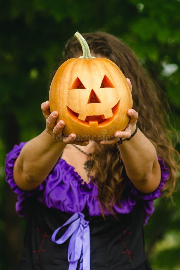 Buitensporige vrouw op Halloween in het bos, die in handenpompoen houden met gesneden gezicht royalty-vrije stock afbeeldingen