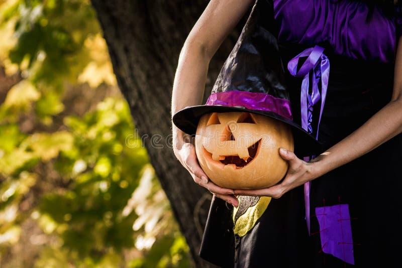 Buitensporige vrouw op Halloween in het bos, die in handenpompoen houden met gesneden gezicht royalty-vrije stock afbeelding