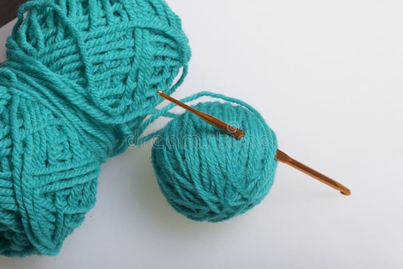 Buizen van draad voor het breien smaragdgroene kleur en haken voor het breien op een witte achtergrond stock afbeeldingen