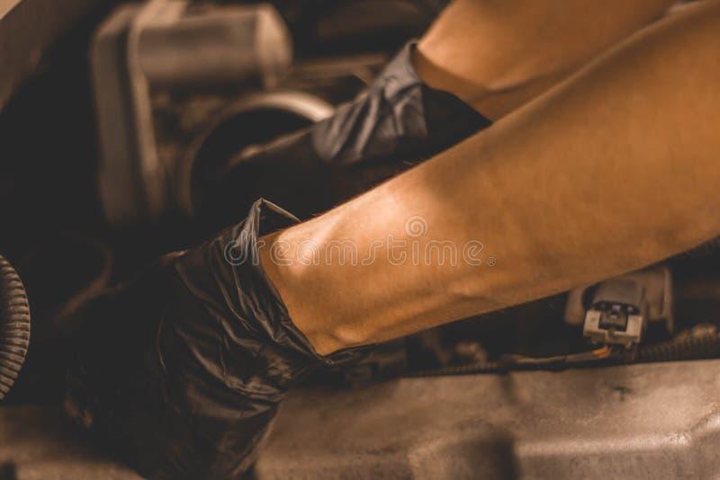 Bujías cambiantes del mecánico de la mujer debajo de la capilla de SUV en la tienda imagenes de archivo