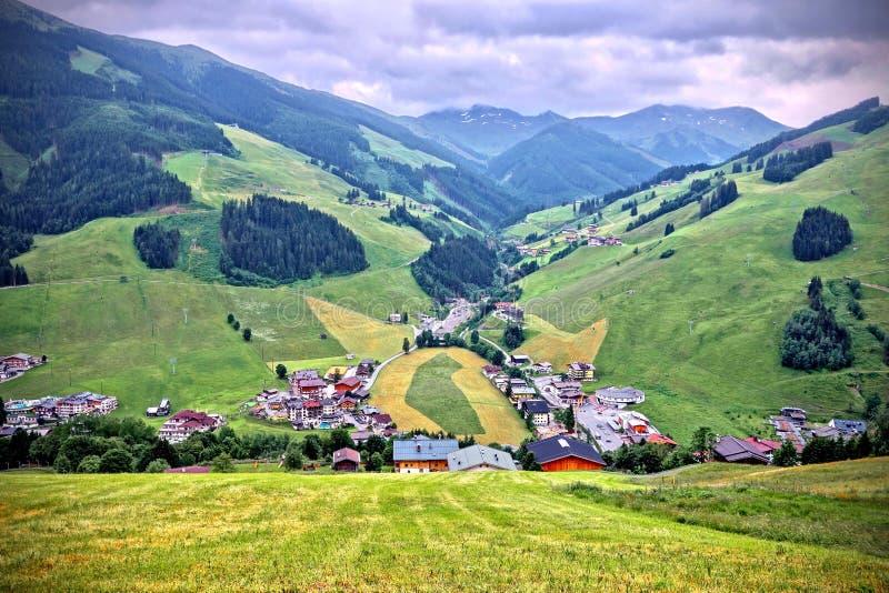 Bujny zielony wysokogórski szczyt pod błękitnym chmurnym niebem w Saalbach, Austria obraz stock