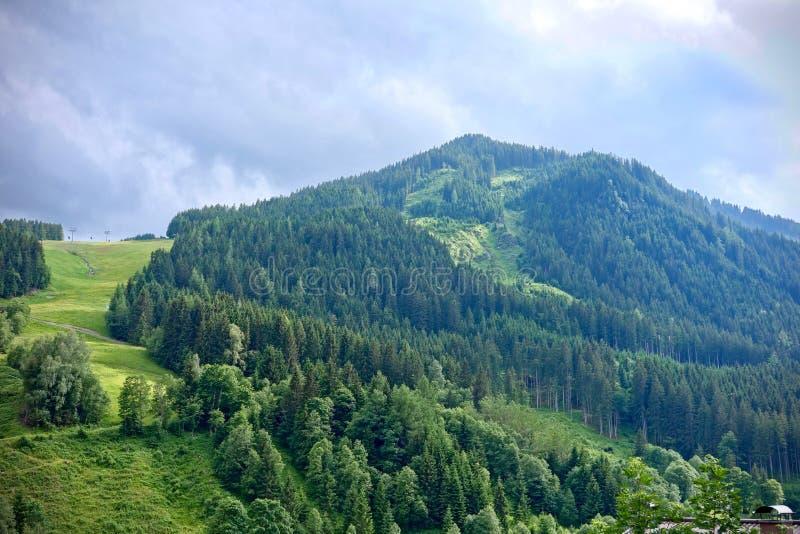 Bujny zielony wysokogórski szczyt pod błękitnym chmurnym niebem w Saalbach, Austria obrazy stock