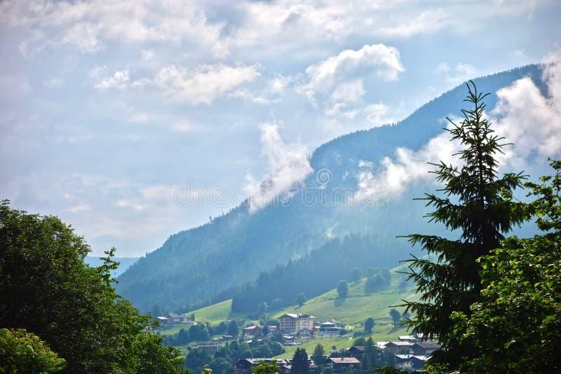 Bujny zielony wysokogórski szczyt pod błękitnym chmurnym niebem w Saalbach, Austria zdjęcie royalty free