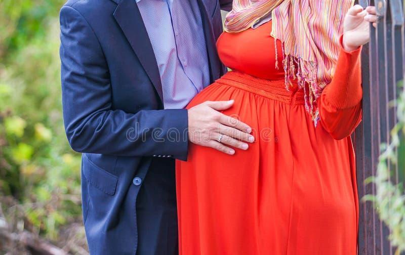 Buk av en gravid kvinna i en röd klänning royaltyfri foto