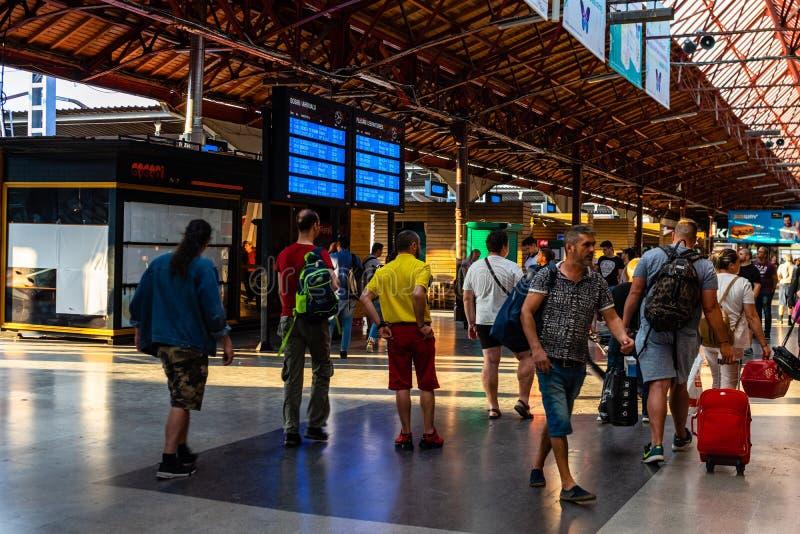Bukarest, Rum?nien - 2019 Reisende, die auf einen Zug in der Abfahrthalle warten und auf einem Abfahrtbrett in Bukarest Nord scha lizenzfreie stockbilder