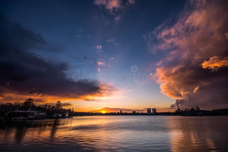 Bukarest-Sonnenuntergang mit drastischen Wolken über Herastrau-Park stockfotos