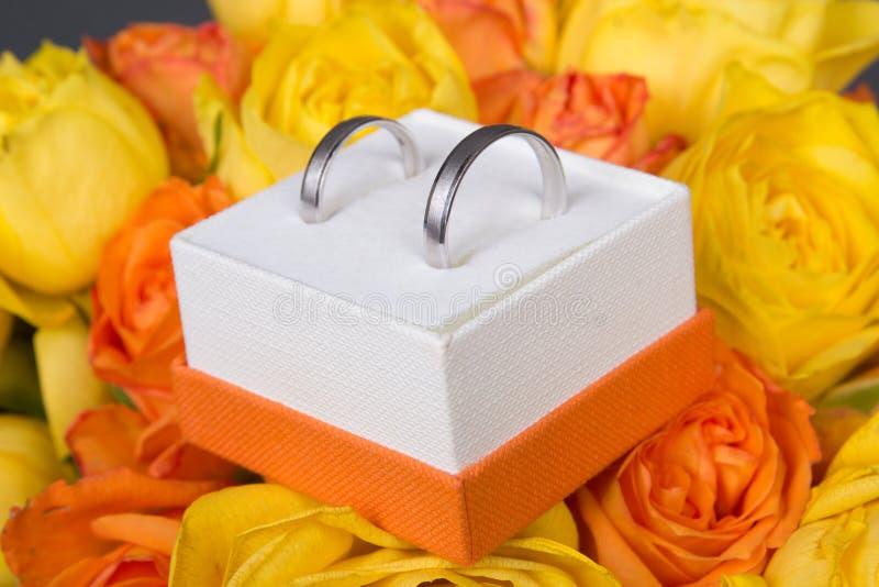 Bukett av apelsin- och gulingrosblommor och vigselringar i b royaltyfria bilder