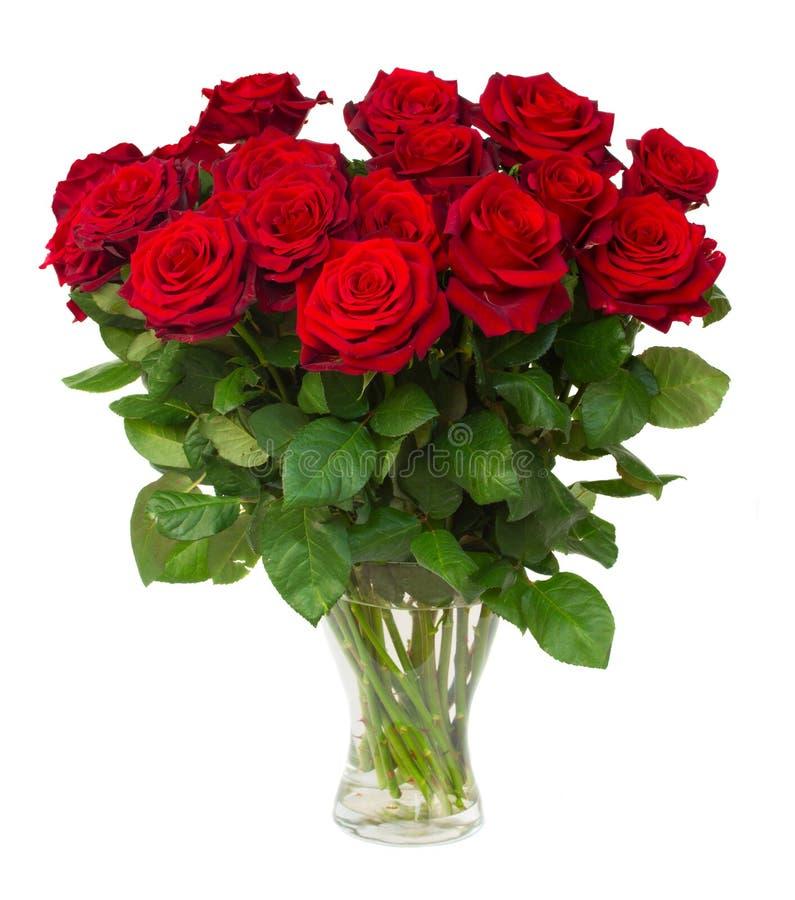 Bukett av att blomstra mörker - röda rosor i vas arkivfoto