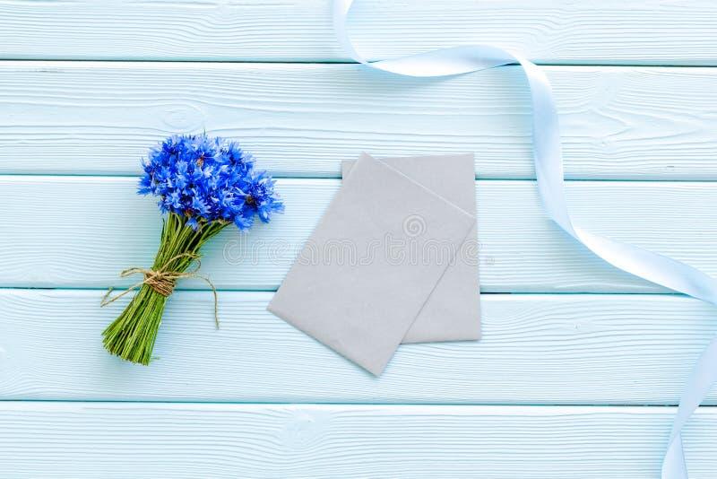 Bukett av blåa blåklinter, kuvert på modell för bästa sikt för mintkaramellgräsplanträbakgrund royaltyfria foton