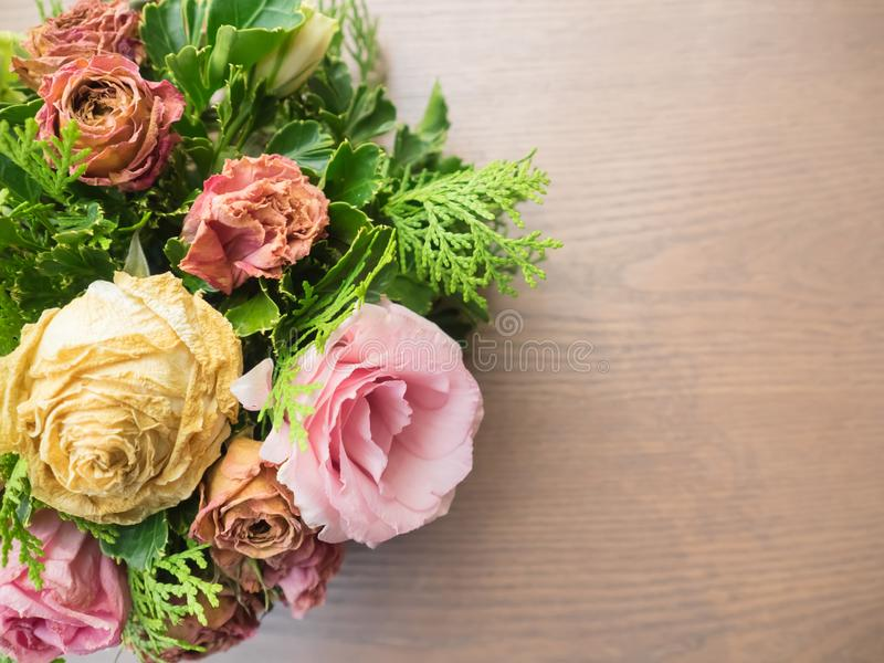Bukett av blandade blommor på träbakgrund, rosor, nejlika, Eustoma, torra blommor royaltyfria bilder