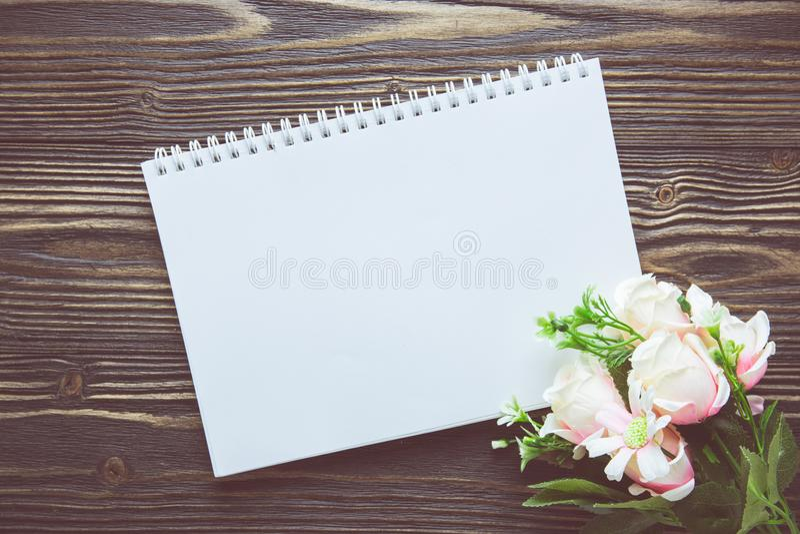 Bukett av blomman och den tomma dagbokanteckningsboken på den lantliga trätabellen med kopieringsutrymme, modellmall med blomman  royaltyfri foto