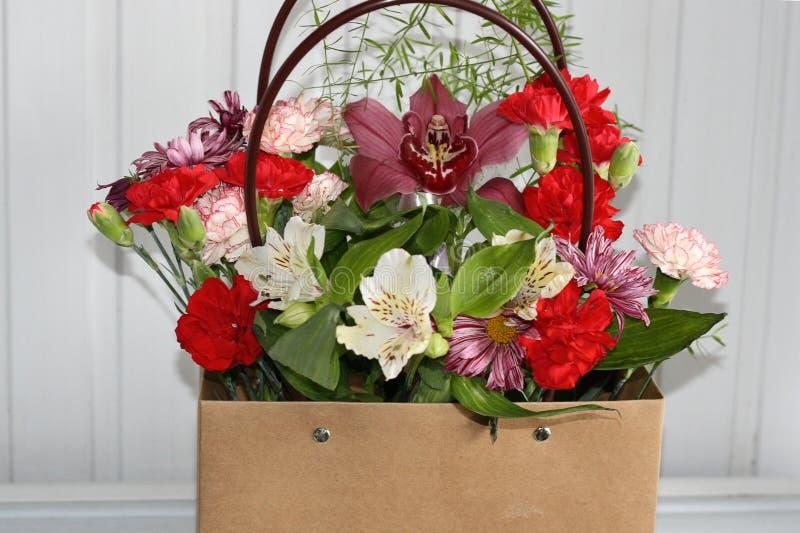 Bukett av blommor i en gåvapåse med handtag arkivfoton