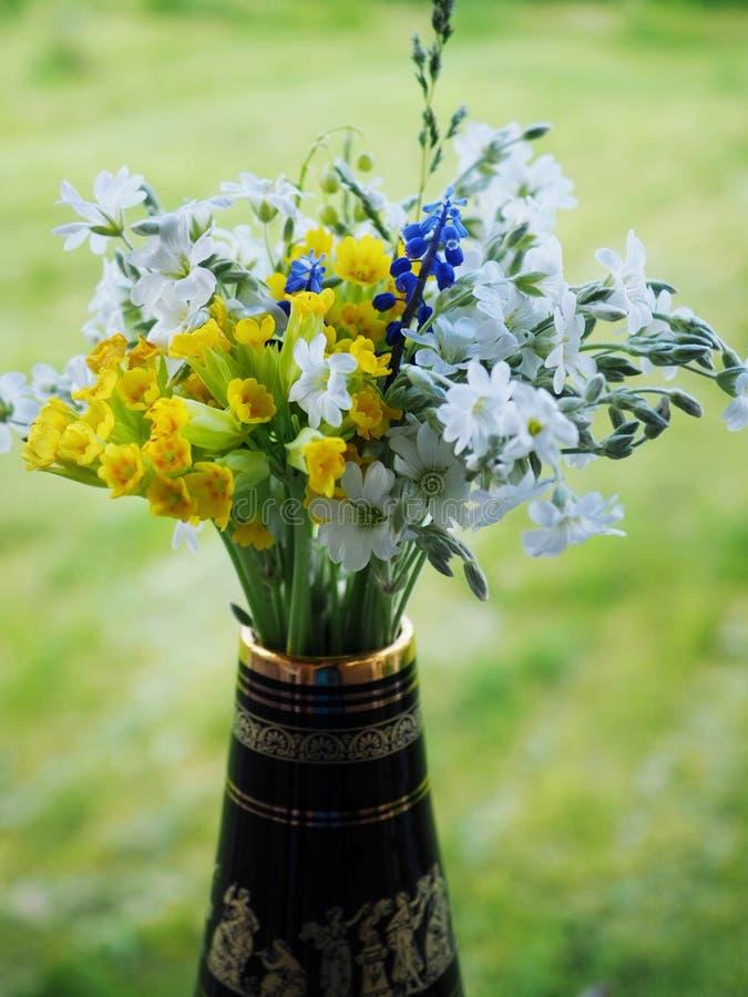 Bukett av blommor i en vas mot grön bakgrund royaltyfria bilder