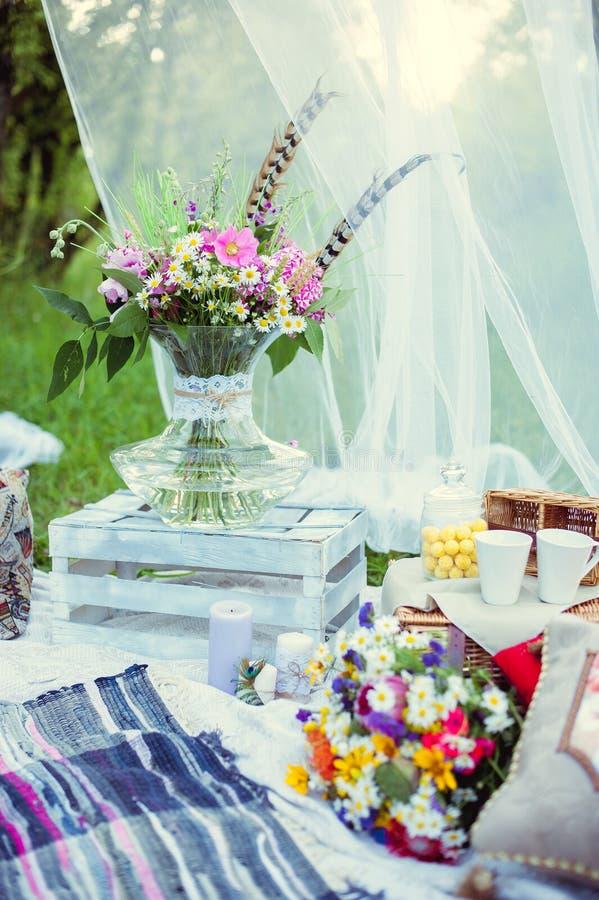 Bukett av blommor i stilen av bohoen i en exponeringsglasvas i natur royaltyfri bild
