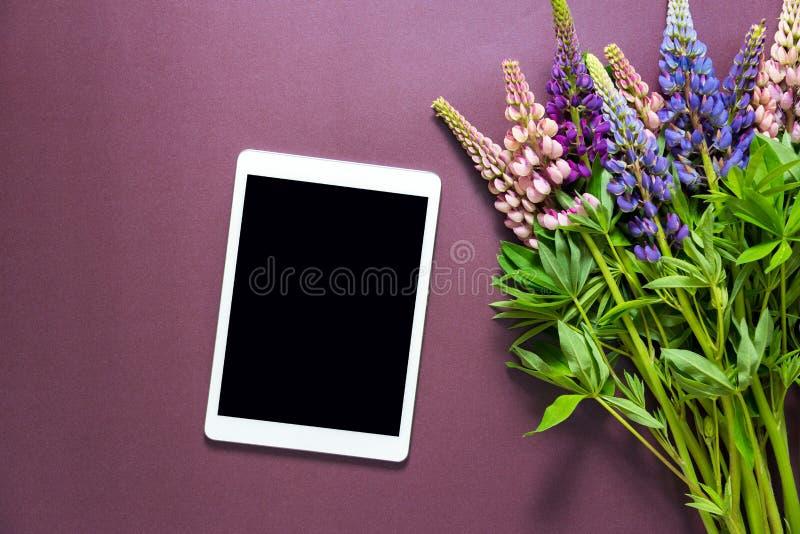 Bukett av blommor på en purpurfärgad bakgrund med en minnestavladator arkivfoton