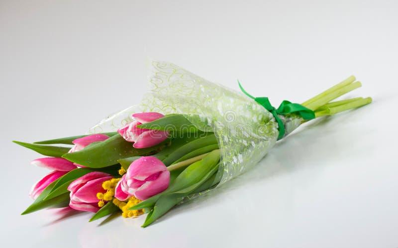 Bukett av blommor: tulpan och mimosa i tsellofannovy skal royaltyfri bild