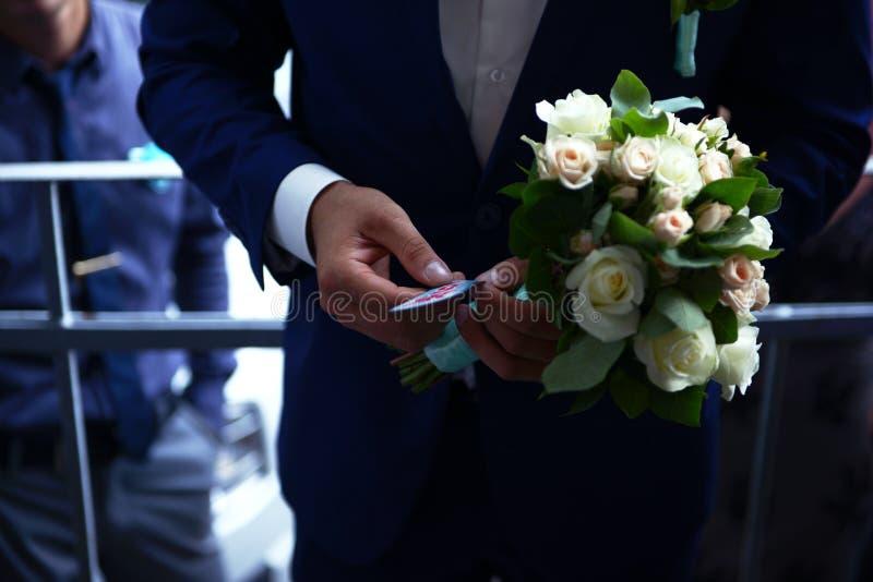 Bukett av bruden i händer av brudgummen royaltyfria bilder