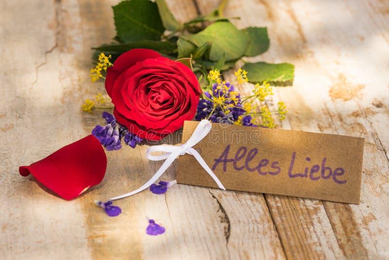 Bukett av den röda den rosblomman och etiketten med tysk text, Alles Liebe, hjälpmedelförälskelse arkivbild