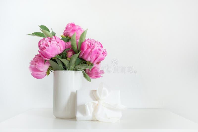 Bukett av den rosa pionen i vas med gåvan på vit Kopiera utrymme f?r text dagblomman ger m?drar mumsonen till royaltyfri bild